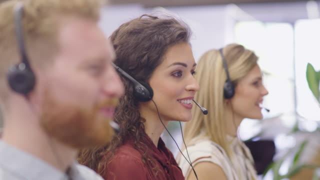 porträt einer lächelnden frau, die im callcenter arbeitet - reliability stock-videos und b-roll-filmmaterial