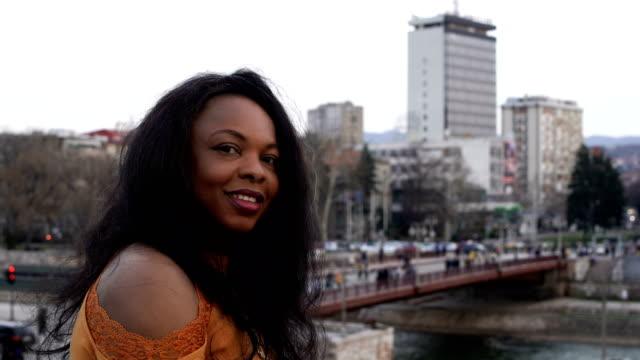 stockvideo's en b-roll-footage met portret van glimlachende jonge zwarte vrouw - curly brown hair