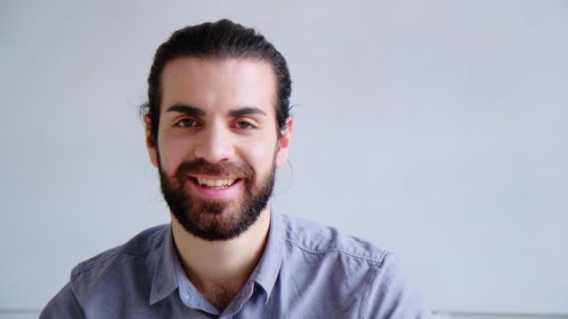 オフィスに座っている笑顔の若いビジネスマンの肖像画 ビデオ