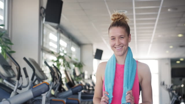 Portrait of Smiling Young Caucasian Woman with Towel at Gym Cheerful Caucasian woman in mid 20s standing with towel around her neck and smiling at camera after workout. wearing a towel stock videos & royalty-free footage