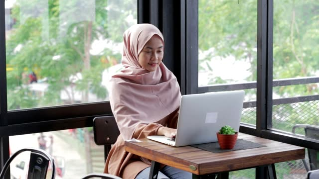 portrait of smiling young muslim woman working on modern laptop in cafe. attractive woman in hijab searching for something in internet. edited and raw. - etnia malese video stock e b–roll
