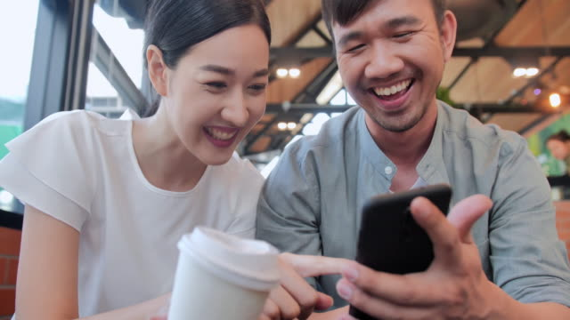 Portrait of smiling young woman at a cafe table looking at smartphone with a friend sitting by.Technology,Friendship,People,Lifestyle,Vision,Business,Innovation,Global concept.South East and East Asia: Couple at a Café video