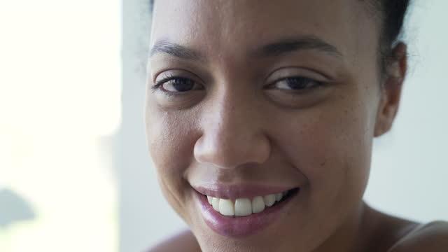 porträtt av leende ung kvinna som sitter på sängen - 30 39 år bildbanksvideor och videomaterial från bakom kulisserna
