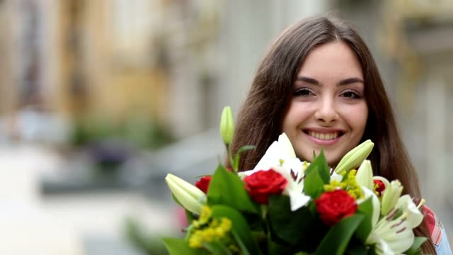 portrait of smiling young woman smelling flowers - bouquet video stock e b–roll