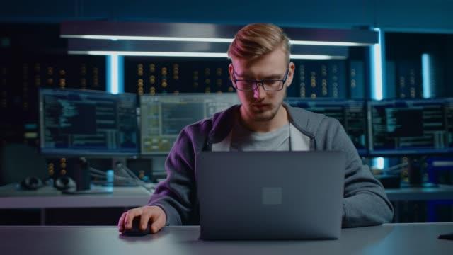 vídeos y material grabado en eventos de stock de retrato de desarrollador de software/hacker/gamer usando gafas y auriculares sentado en su escritorio y trabajando/jugando en el ordenador portátil. en el entorno de fondo oscuro de alta tecnología con múltiples pantallas. - equipo informático