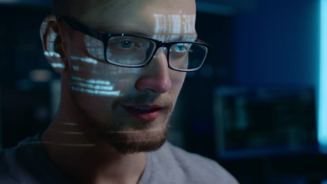 portrait of software developer / hacker wearing glasses working on computer, projected code numbers and characters reflect on his face. dark room full of technology. zoom in shot - hacker стоковые видео и кадры b-roll