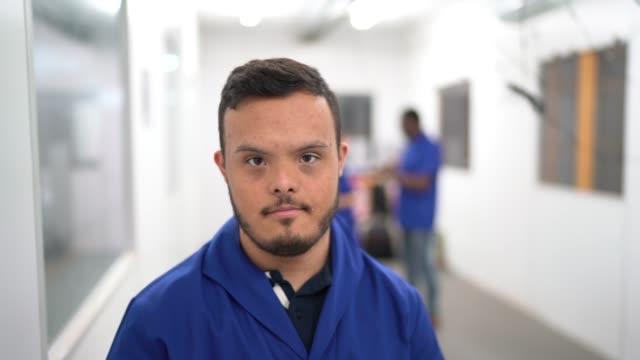 vídeos de stock e filmes b-roll de portrait of special needs employee in industry - capacidades diferentes