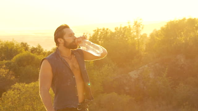 Portrait of strong man drinks and pours himself from bottle with water. Slowly video