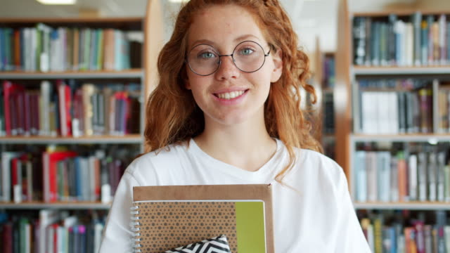 Portrait of student pretty girl holding books in university library smiling Portrait of joyful student pretty girl holding books in university library smiling looking at camera indoors alone. People, education and emotions concept. redhead stock videos & royalty-free footage