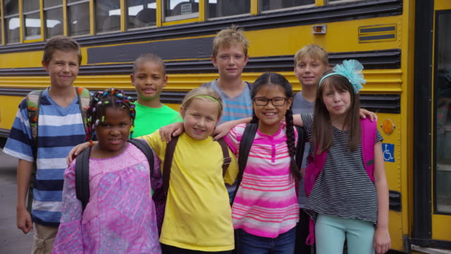 Portrait of students in front of school bus video