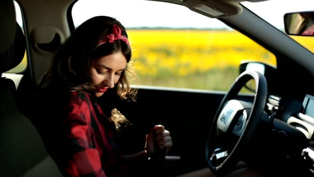 Portrait of stunning woman fastening car seatbelt video