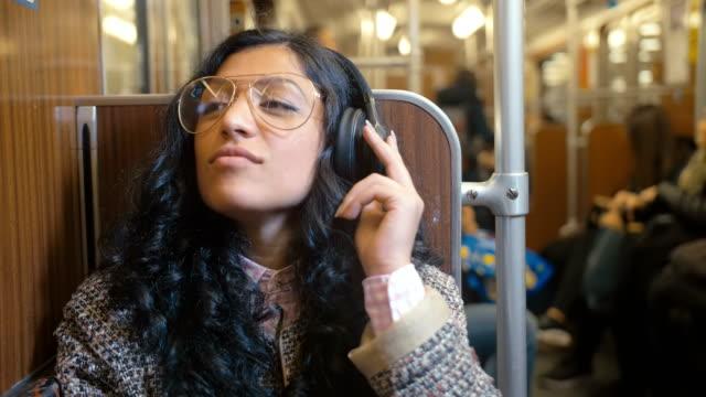 vídeos y material grabado en eventos de stock de retrato de elegante y de moda morena monta en un coche del tren y escucha música con auriculares con placer que video se redujo a 2 veces la velocidad real - escuchar
