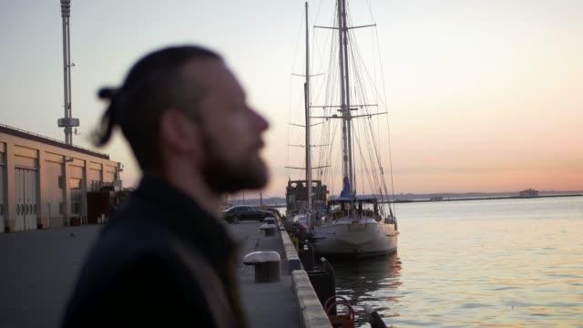porträt von stilvollen hipster mann am meer port hintergrund während des sonnenuntergangs, beiseite - introspektion stock-videos und b-roll-filmmaterial