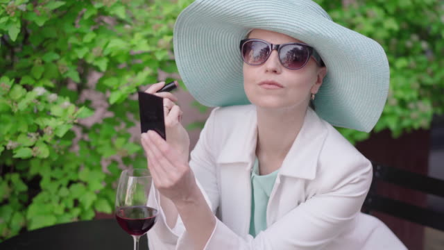 Portrait of stylish woman in turquoise hat and sunglasses applying lipstick. Beautiful Caucasian lady admiring reflection in hand mirror as sitting outdoors with glass of red wine. Leisure, beauty.