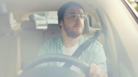 vídeos y material grabado en eventos de stock de retrato de hombre joven elegante unidades de coche, tiene diversión, escucha música y bailes. cámara de disparo hecho desde el parabrisas delantero. - conducir