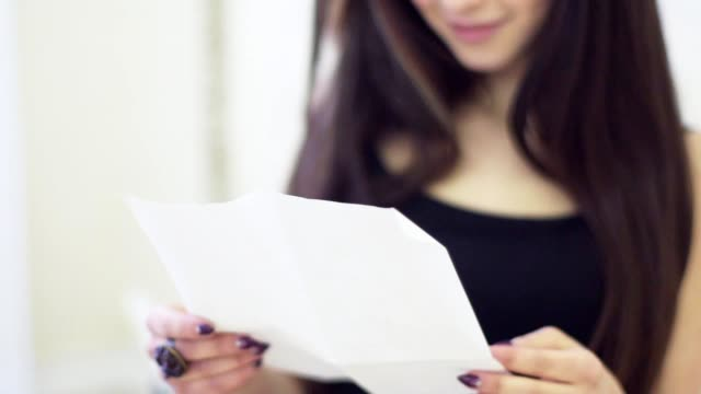 Portrait of stylish young woman with brown hairs reading letter in apartment video