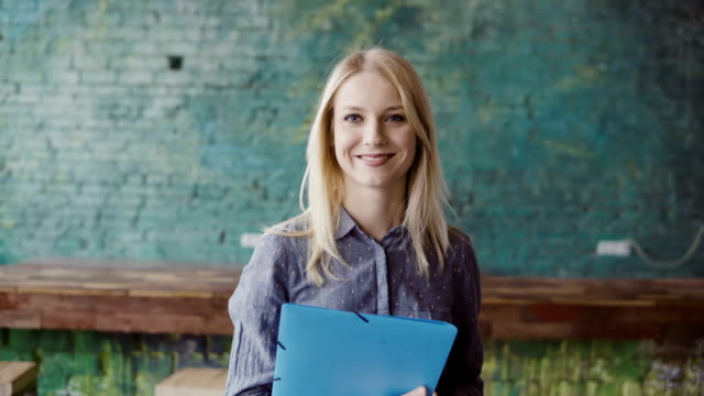 Portrait of successful beautiful blonde businesswoman at loft coworking space. Female holds the document, smiling