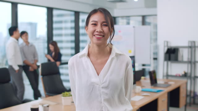 vídeos de stock e filmes b-roll de portrait of successful beautiful executive businesswoman smart casual wear looking at camera and smile, arms crossed in modern office workplace. - etnia asiática