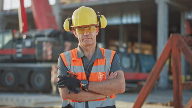 Portrait of Successful Builder / Worker / Contractor Wearing Hard Hat and Safety Vest Standing on a Commercial Building Construction Site, Crosses Arms Confidently. In the Background Crane Machinery Portrait of Successful Builder / Worker / Contractor Wearing Hard Hat and Safety Vest Standing on a Commercial Building Construction Site, Crosses Arms Confidently. In the Background Crane Machinery work helmet stock videos & royalty-free footage
