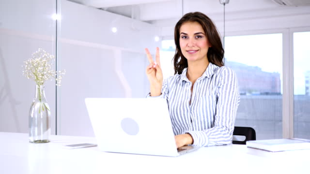 portrait of successful young woman gesturing victory sign at work - campionato video stock e b–roll