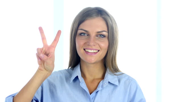 portrait of successful young woman gesturing  victory sign - campionato video stock e b–roll