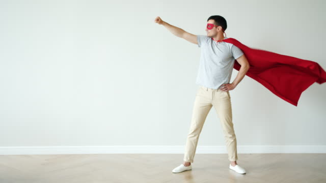 Portrait of super hero in fluttering red cape and mask standing with raised arm video