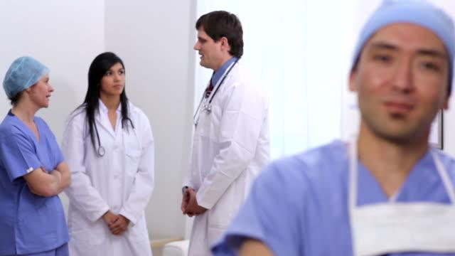Retrato de cirujano con otro personal médico en el fondo - vídeo