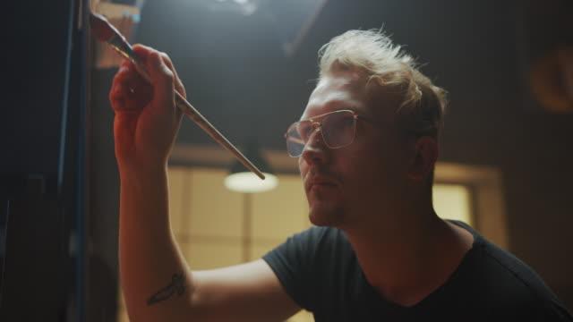 porträt von talentierten künstler arbeiten an abstrakten malerei, verwendet malpinsel, um gewagt emotionale moderne bild zu schaffen. dark creative studio große leinwand steht auf easel beleuchtet. side view close-up shot - künstlerischer beruf stock-videos und b-roll-filmmaterial