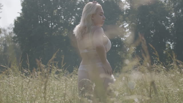 portrait of tanned plus size caucasian woman in lace underwear posing on summer meadow on sunny day. confident young overweight lady spinning with thoughtful facial expression. cinema 4k prores hq - body positive video stock e b–roll
