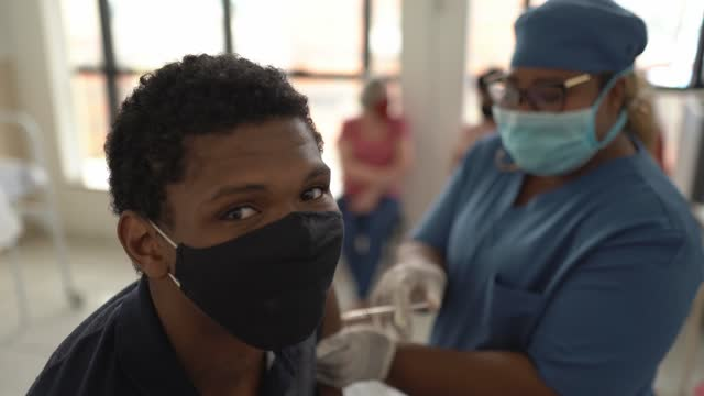 Portrait of teenager boy being vaccinated - wearing face mask video