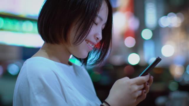 ピアスとカジュアルな服を着て魅力的な日本の女の子の肖像画は、スマート フォンを使用しています。バック グラウンドでは、大都市の広告は、夜のライトの輝きを看板します。 - スマートフォン点の映像素材/bロール