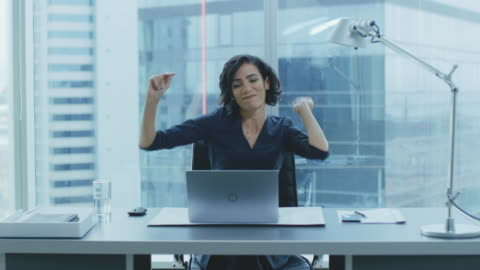 vídeos de stock e filmes b-roll de portrait of the beautiful businesswoman dancing while sitting at her desk. successful and happy woman celebrating record sales. - felicidade