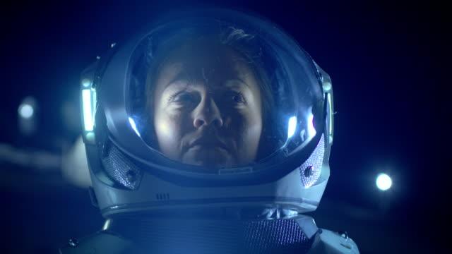 Retrato del astronauta mujer hermosa en el planeta extraterrestre mirando a su alrededor con asombro. En los cuartos de estar de fondo. Viajes espaciales, exploración y concepto de colonización del Sistema Solar. - vídeo
