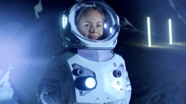Retrato de hermosa mujer astronauta en el planeta extraterrestre mirando con asombro, sonrisas. En el hábitat de vida del fondo. Viajes espaciales, exploración y concepto de colonización del Sistema Solar. - vídeo