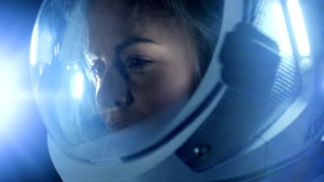 porträt des schönen weiblichen astronauten platz gehen, schaut sich um in wunder, space station leuchtet ihr gesicht. raumfahrt, exploration und sonnensystem kolonisation konzept. - raumanzug stock-videos und b-roll-filmmaterial