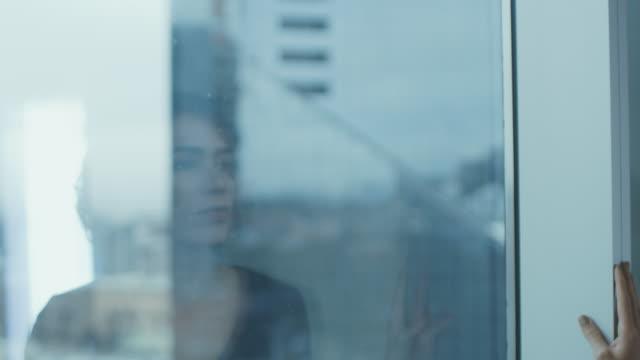 美麗的年輕女商人的肖像, 若有所思地走出她的辦公室視窗。有信心和有吸引力的西班牙裔婦女考慮她的商業專案。 - 看窗外 個影片檔及 b 捲影像