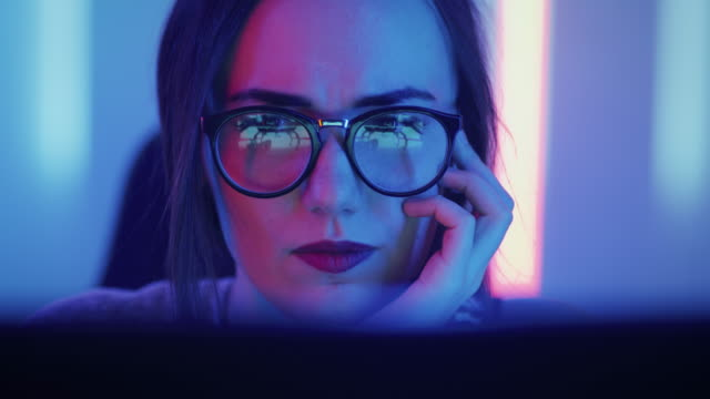 portrait of the beautiful young girl sitting before computer, browsing in internet, playing online games, streaming. cute girls wearing glasses in the cool retro neon lit room. - designers video stock e b–roll