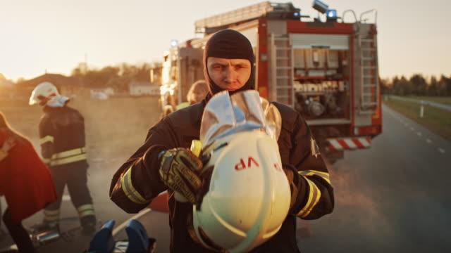 Porträt des tapferen Feuerwehrmanns, der seinen Helm abnimmt. Im Hintergrund Mutige Helden Sanitäter und Feuerwehrleute Rettungsteam bekämpfen Feuer, Rauch und retten Menschenleben – Video