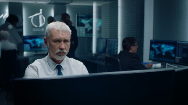 portrait of the concerned senior expert working on computer in the monitoring control room with teams solving problems in the background. - politica e governo video stock e b–roll