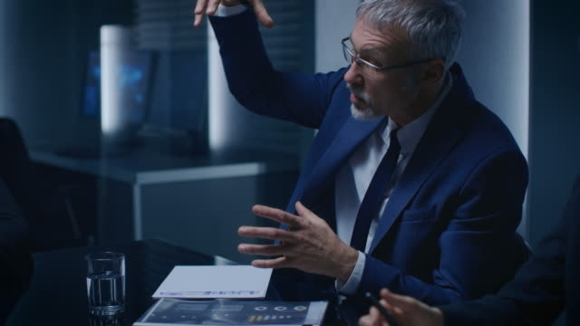 vídeos de stock e filmes b-roll de portrait of the corporate businessman having heated debate with his business partners during weekly meeting. serious business people: problem solving, negotiating and strategizing in the conference room. - liderança
