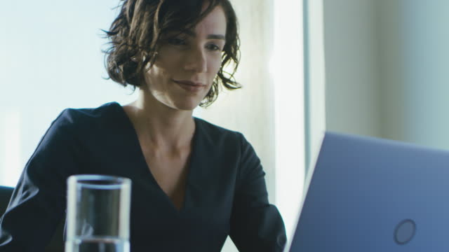 portrait of the focused female ceo working on a laptop. happy successful businesswoman doing her important business job beautifully. - business people stock videos & royalty-free footage