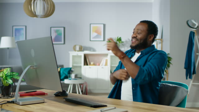 vídeos de stock e filmes b-roll de portrait of the handsome black man dancing while sitting at his workplace. young man having fun at home. - celebrate
