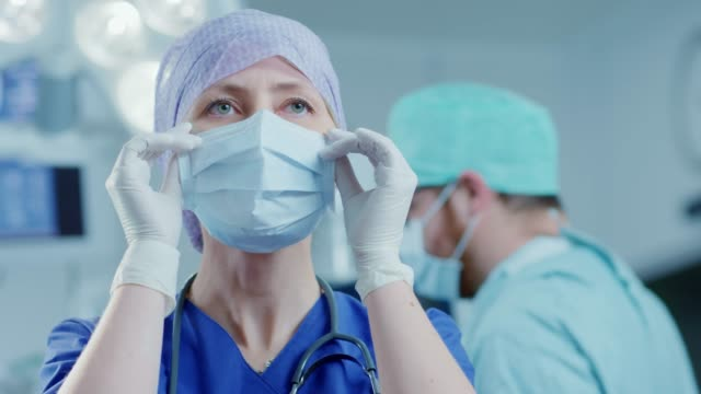 vídeos de stock e filmes b-roll de portrait of the professional nurse / medical assistant taking off surgical mask after successful operation. in the background modern hospital operating room. - remover