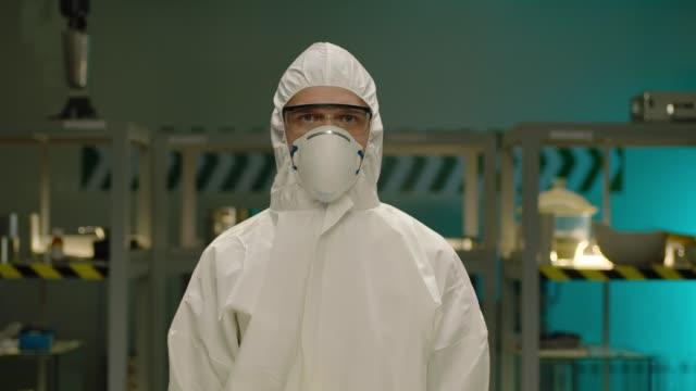 profesyonel bilim adamı portresi . modern laboratuvarın arka planda . tıbbi koruyucu tulum ile genç bir adam kimyager veya doktor portresi . arri alexa sinema kamerasında çekim - first responders stok videoları ve detay görüntü çekimi