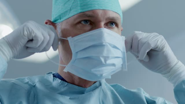 portrait of the professional surgeon putting on surgical mask in the background modern hospital operating room. - face mask stock videos & royalty-free footage