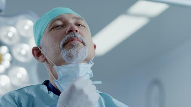 portre profesyonel cerrah alarak başarılı işlemi sonra ameliyat maskesi kapalı. arka plan modern hastane ameliyat odasında. - cerrah stok videoları ve detay görüntü çekimi