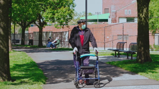 Portrait of the senior 90-years-old man wearing protective mask and gloves because of the COVID-19 pandemic walking outdoor in a park using a walker and maintaining social distancing.