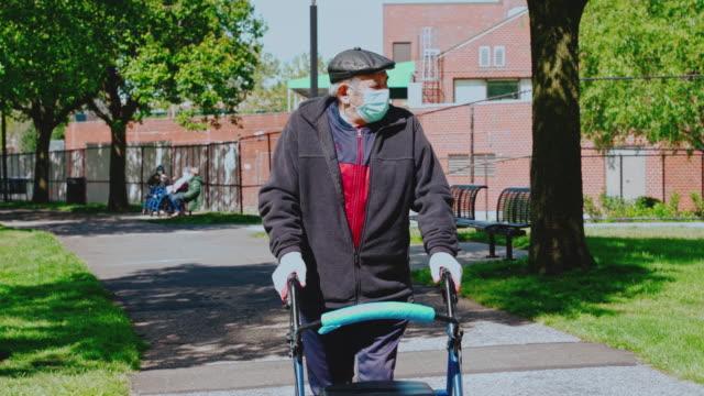 這位90歲的老人戴著防護面具和手套的肖像,因為covid-19大流行,在公園裡用步行者散步,保持社會疏遠。 - 廣場 個影片檔及 b 捲影像