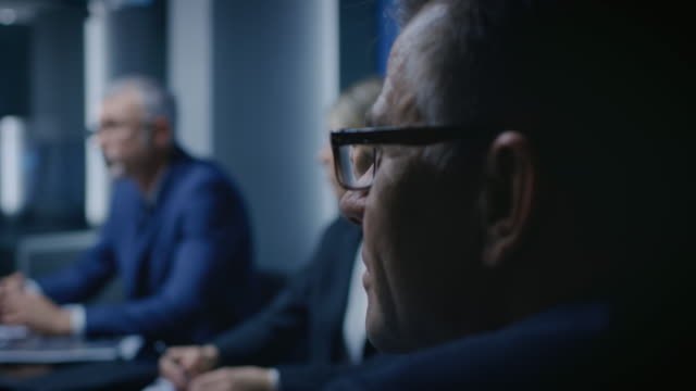 portrait of the senior member of the board of the directors listening to his business partners on a meeting. - politica e governo video stock e b–roll