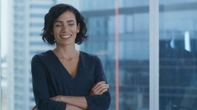 porträtt av den framgångsrika spansktalande affärskvinna korsar armarna och leende. vackra kvinnliga verkställande står i hennes kontor. - affärskvinna bildbanksvideor och videomaterial från bakom kulisserna